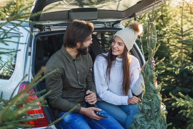 Casal agradável sentado no porta-malas do carro olhando para a maravilhosa árvore de natal que escolheram para as férias