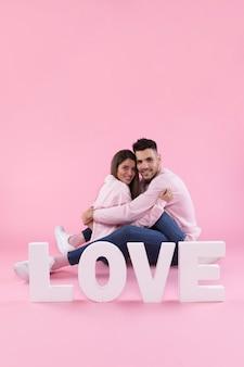 Casal alegre abraçando perto de escrever amor