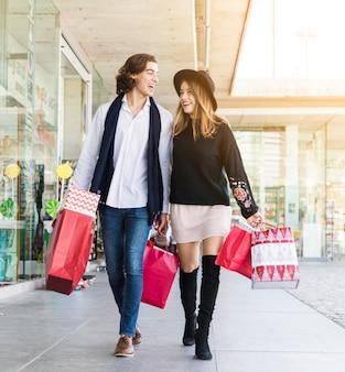 Casal alegre andando com sacolas de compras
