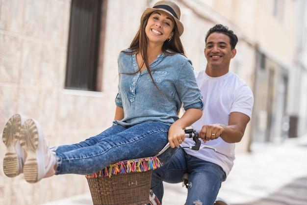 Casal alegre andando de bicicleta ao ar livre na cidade. homem com mulher encantada, sentado no guidão, enquanto andava de bicicleta na cidade. casal despreocupado curtindo um passeio de bicicleta na rua da cidade