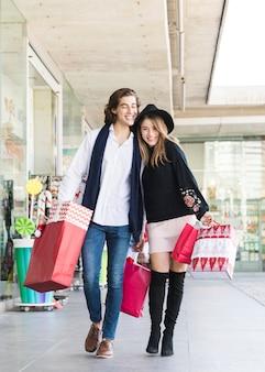 Casal alegre andando na rua com sacolas de compras