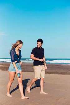 Casal alegre andando perto do mar