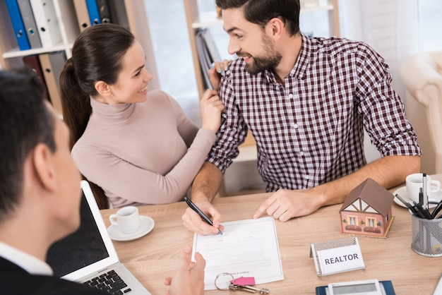 Casal alegre assina contrato para compra de casa nova