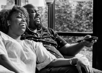 Casal alegre assistindo TV juntos