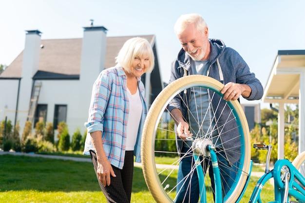 Casal alegre. casal de esposa e marido idosos se sentindo alegres enquanto consertam uma bicicleta do lado de fora
