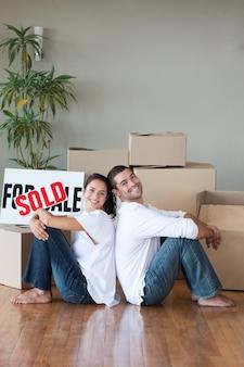 Casal alegre com caixas de desembalagem se mudando para uma nova casa