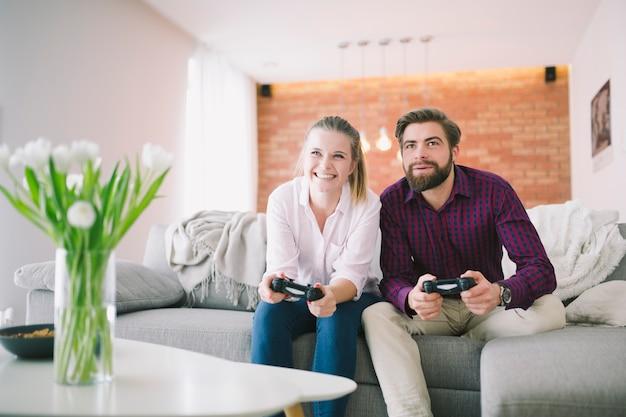 Casal alegre com controladores em casa