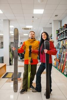 Casal alegre com esquis nas mãos, compras na loja de esportes. estilo de vida extremo na temporada de inverno, loja de lazer ativo, clientes comprando equipamentos de esqui