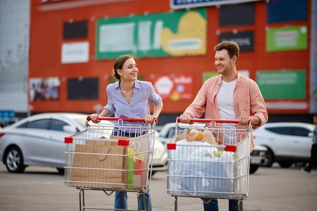 Casal alegre com malas em carrinhos no estacionamento