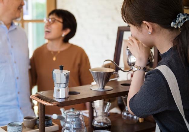 Casal alegre com mulher servindo-lhes bebidas