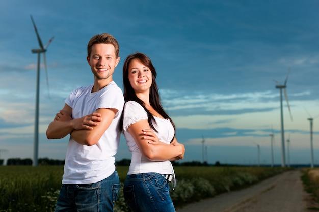 Casal alegre, com os braços cruzados posando na frente de moinhos de vento