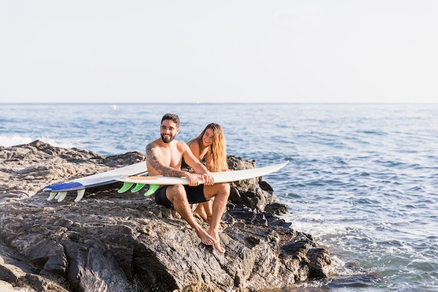 Casal alegre com pranchas de surf na costa rochosa