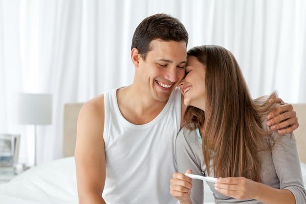 Casal alegre com um teste de gravidez no quarto