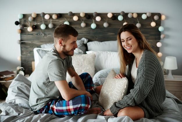 Casal alegre conversando na cama