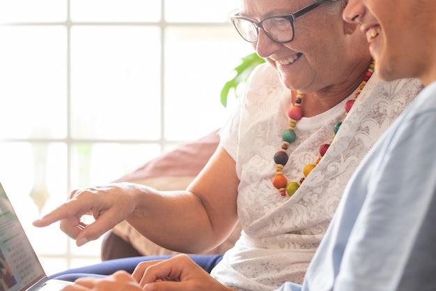 Casal alegre de avó e neto adolescente sentados juntos no sofá em casa, olhando com diversão para o mesmo laptop e sorrindo. conceito de amor e amizade