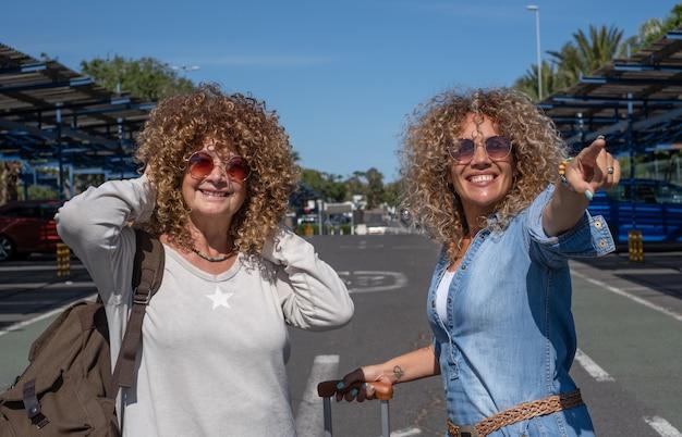 Casal alegre de mulheres encaracoladas com bagagem e mochila pronta para viajar, sorrindo, olhando para a câmera
