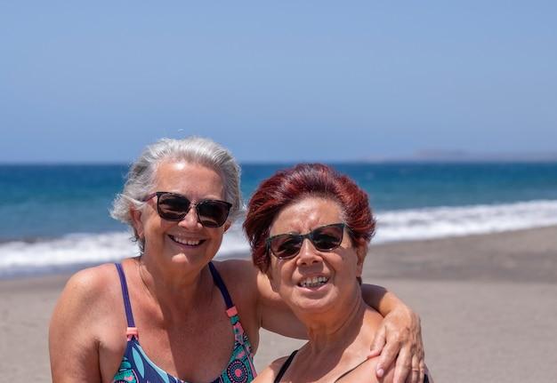 Casal alegre de mulheres sêniors em amizade, curtindo a praia juntos sob o sol com ondas e o mar azul no fundo - aposentados ativos e conceito de férias