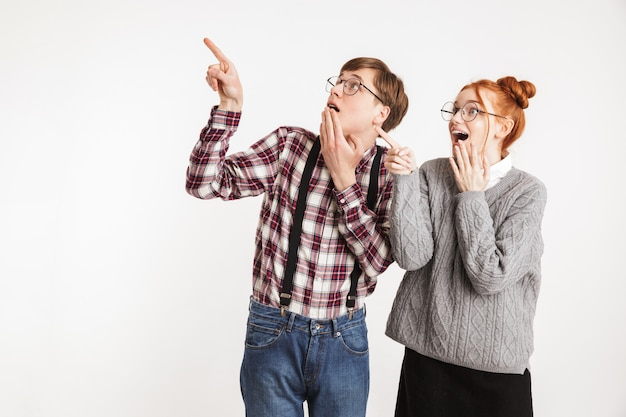 Casal alegre de nerds da escola apontando o dedo