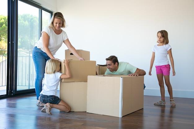 Casal alegre de pais e duas meninas se divertindo enquanto abrem caixas e desempacotam coisas em seu novo apartamento vazio