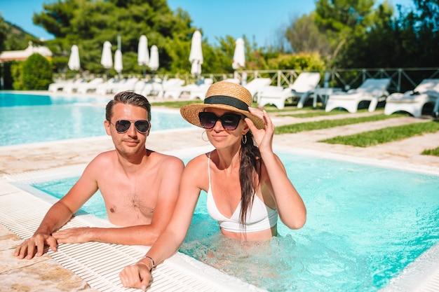 Casal alegre, descansando em uma piscina