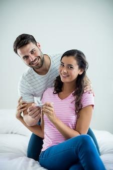 Casal alegre descobrindo o resultado de um teste de gravidez no quarto de casa