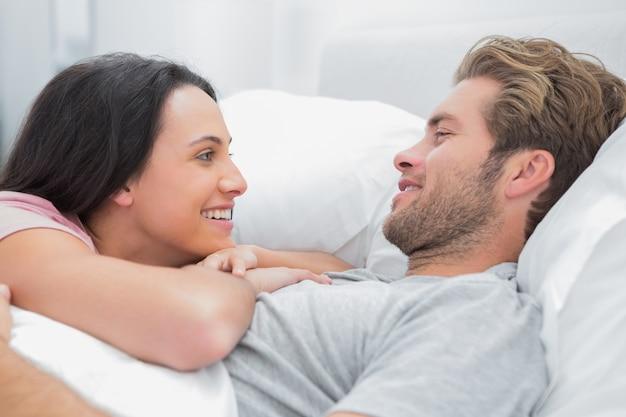 Casal alegre, despertando e olhando um para o outro