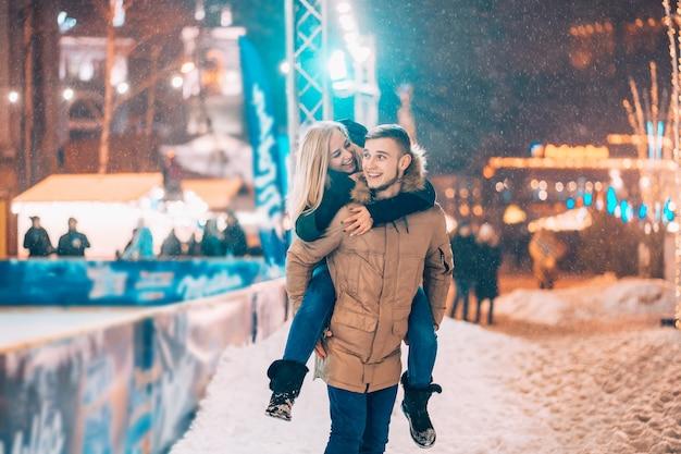 Casal alegre e brincalhão em roupas de inverno quente estão brincando