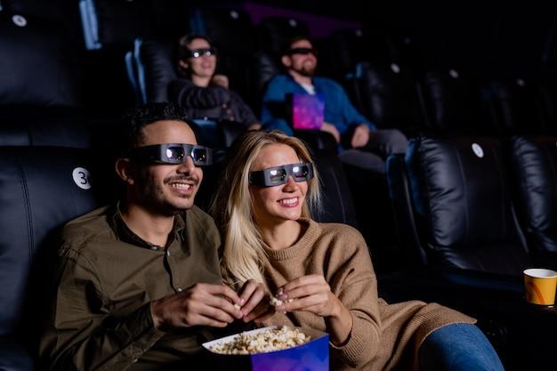 Casal alegre em óculos 3d comendo pipoca enquanto está sentado em poltronas em frente a uma tela grande no cinema escuro