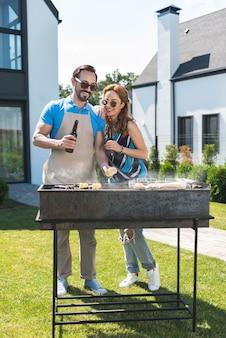 Casal alegre em pé junto preparando um churrasco