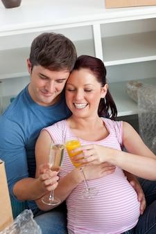 Casal alegre esperando um bebê bebendo e sentado no chão