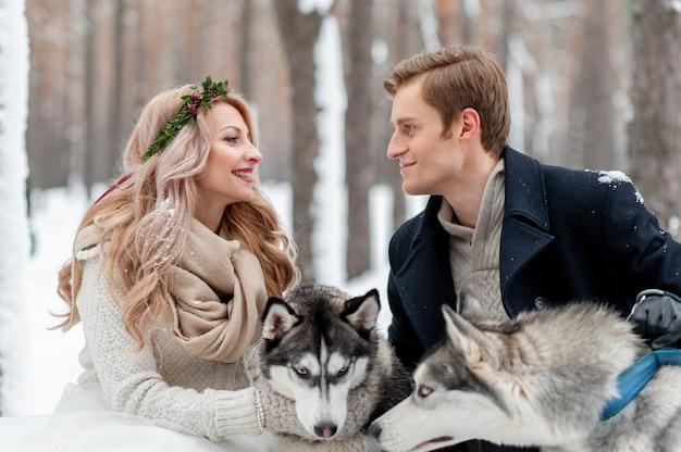 Casal alegre está jogando com husky siberiano no bosque nevado. arte do casamento no inverno