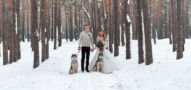 Casal alegre está jogando com husky siberiano no bosque nevado. casamento de inverno.