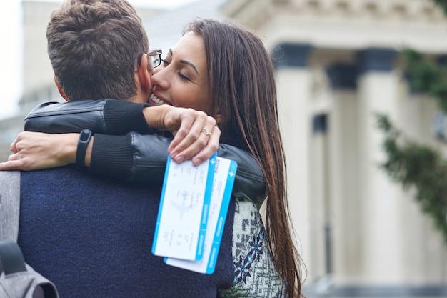 Casal alegre feliz abraçando e mostrando os bilhetes a voar.