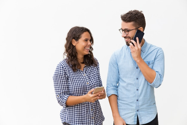 Casal alegre feliz usando telefones móveis