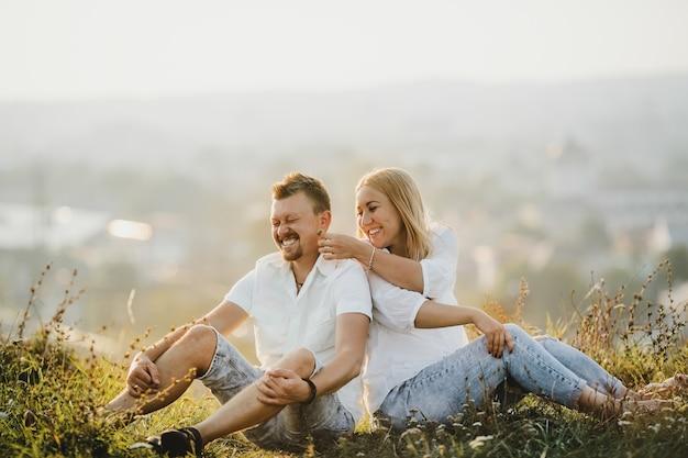 Casal alegre fica lado a lado no gramado verde em lindo dia de verão