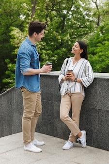 Casal alegre, homem e mulher com copos de papel, sorrindo e conversando em pé na escada ao ar livre