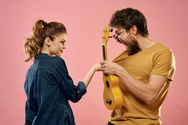 Casal alegre homem e mulher com ukulele, estilo de vida em uma parede rosa