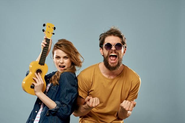 Casal alegre homem e mulher com ukulele, estilo de vida