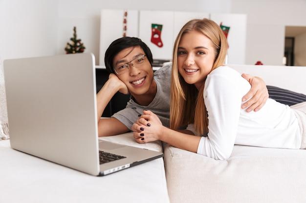 Casal alegre, homem e mulher deitados juntos na cama em casa, com laptop prateado