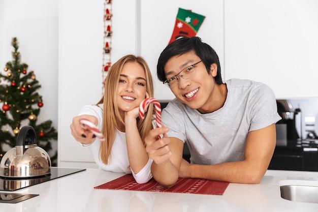 Casal alegre, homem e mulher em pé na cozinha bem iluminada, segurando doces de natal