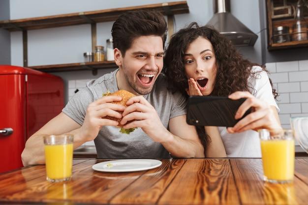 Casal alegre, homem e mulher, usando telefone celular enquanto comem hambúrguer durante o café da manhã na cozinha de casa