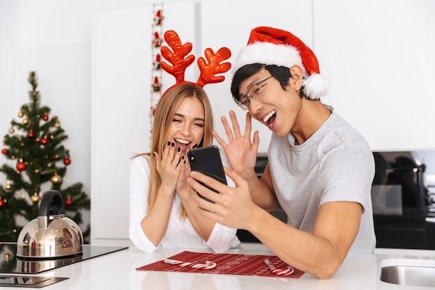 Casal alegre, homem e mulher vestindo roupas de natal, em pé na cozinha bem iluminada e usando telefone celular