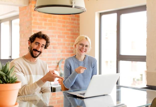 Casal alegre, mulher se sentindo feliz e apontando para o lado e para cima, mostrando o objeto no espaço da cópia