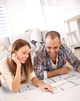 Casal alegre, olhando para o plano de construção de casa