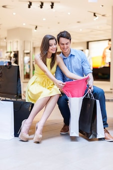 Casal alegre olhando roupas novas