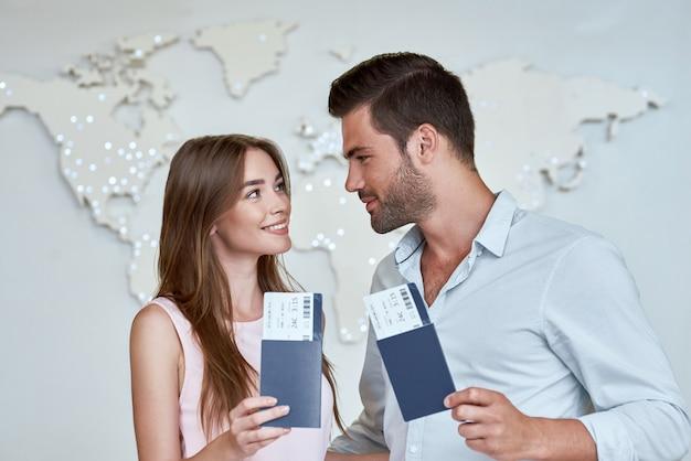 Casal alegre olhando um para o outro com passaporte e passagens aéreas