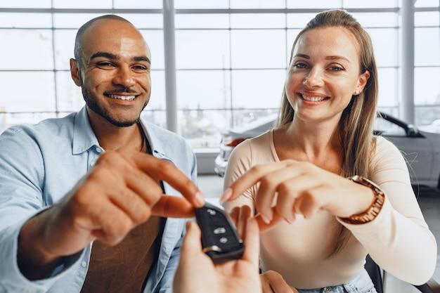 Casal alegre pegando as chaves de seu carro novo na concessionária de uma vendedora