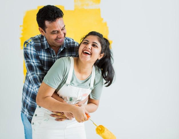 Casal alegre pintando as paredes amarelas
