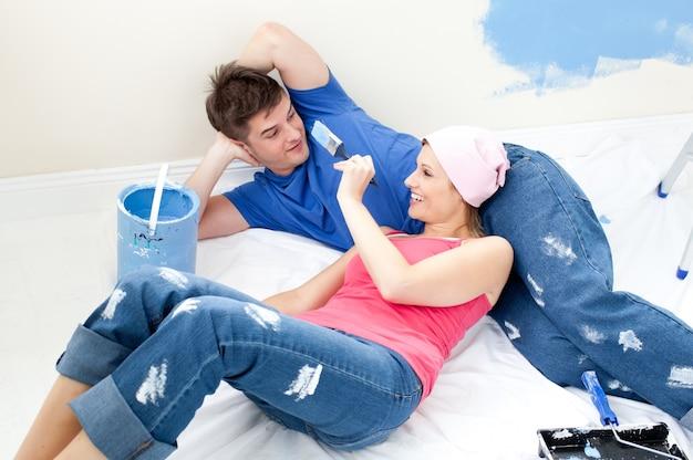 Casal alegre pintando um quarto em sua nova casa