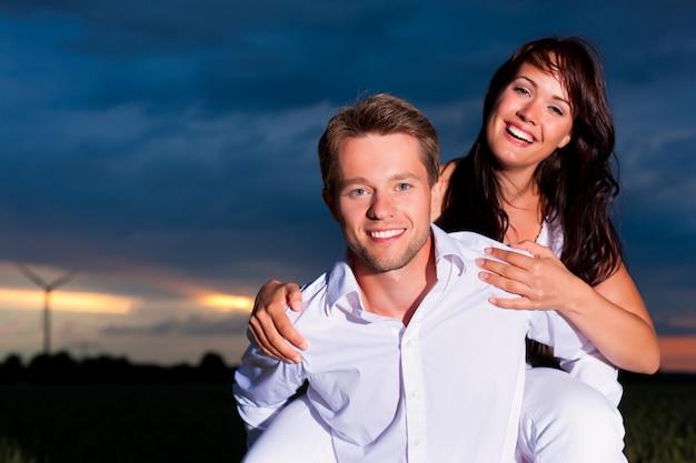 Casal alegre posando na frente do moinho de vento ao pôr do sol